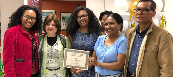 CHST instructor Irma Kramer presents Belicia Bethel (pictured with her family) the Gertrud Lenzer Founder's Outstanding Senior Award