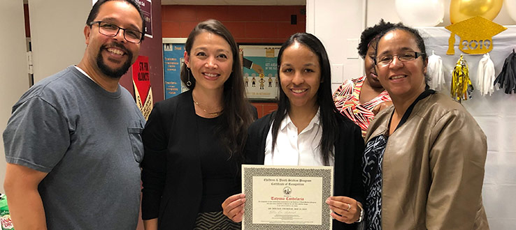 CHST faculty Dr. Erika Niwa presents Tatyana Candelaria (pictured with her family) the Certificate of Recognition Senior Award