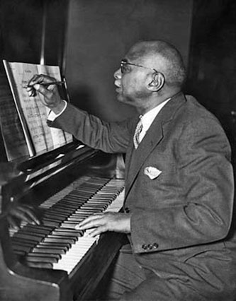 <p>W.C. Handy composing at the piano, courtesy of <a href=