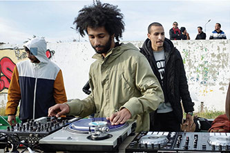 <p>Rami Mhazres (aka DJ Superflava) performs at an outdoor jam that brought together Tunisian and American hip-hop artists through the Next Level cultural diplomacy program. Tunis, Tunisia, 12 February 2017. Photo by the author.</p>