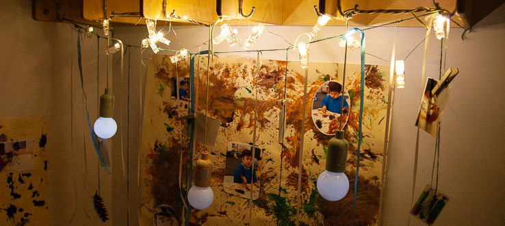 A colorful mural is on display in the Ones Room, a painting by the children, celebrated by hanging lights and ribbon.