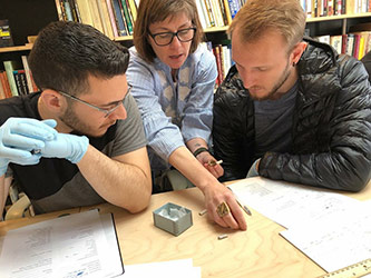 Professor Britt working with students in her lab with historic artifacts from various contexts of New York City, exposing students to archaeological methods and the rich history of the city.
