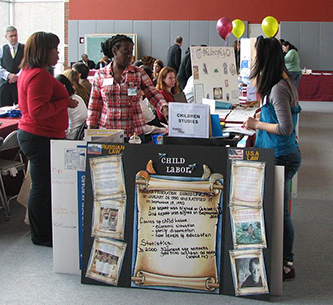 <p>Members of Children First Club staff a table at a Brooklyn College Open House.</p>