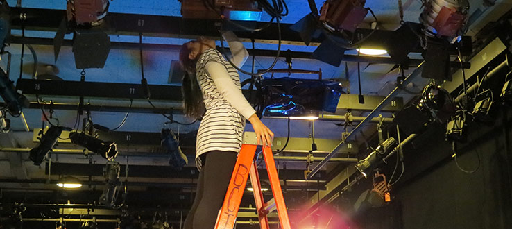 1<p>An MFA student works on the Studio B lighting grid.</p>