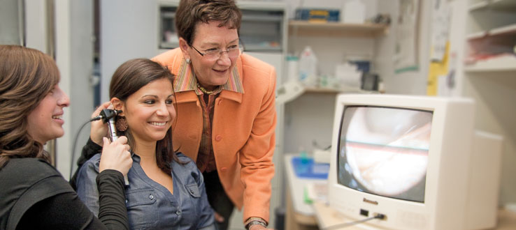 Graduate students work on high-tech equipment to study speech and hearing disorders.