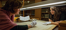 Two female students examining an old book with protective gloves in the library.