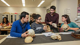 Anthropology professor and students examining fossils in the lab.