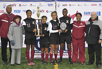 <p>Coach Patrick Horne and Brooklyn College President Karen L. Gould with the new CUNYAC champions. Far right, Athletics Director Bruce Filosa.</p>
