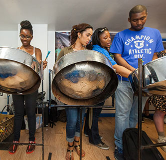 <p>Students take a lesson on playing the steelpan. </p>