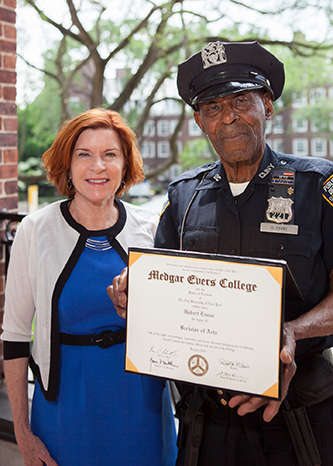 <p>Officer Hubert Evans sharing his degree with President Karen L. Gould. </p>