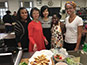 <p>From left: Health and Nutrition Club Vice President Naudia Jones; Professor Patricia Cai, a lecturer in kinesiology in the Department of Athletics; health and nutrition major Letao Wang; and health and nutrition major Patricia Pauyo surround Natasha Griffiths, a screenwriting student at the Feirstein Graduate School of Cinema. Griffiths cooked Jamaican ackee and saltfish with breadfruit for the event.</p>