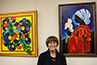<p>Patricia Brintle stands between two of her works—<em>Rassemble</em> (2011. Acrylic on canvas, 36 x 36) and <em>Callas Four</em> (undated. Acrylic on canvas, 36x24). Brintle is a self-taught artist who was born and raised in Haiti and immigrated to the United States in 1964. Her colorful style reflects her native land; she favors bright, vivid, and vibrant colors and uses much symbolism in her work. </p>