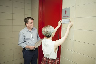 <p>Adjunct English Professor David P. McKay '93 watches as senior and LGBTA President Sami Binder installs the first gender-inclusive restroom sign.</p>