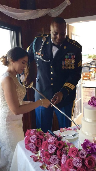<p>The highly decorated James, in full regalia, and his wife Damaris Rosado-James '10, use his saber to cut their wedding cake at a ceremony that took place on September 30.</p>