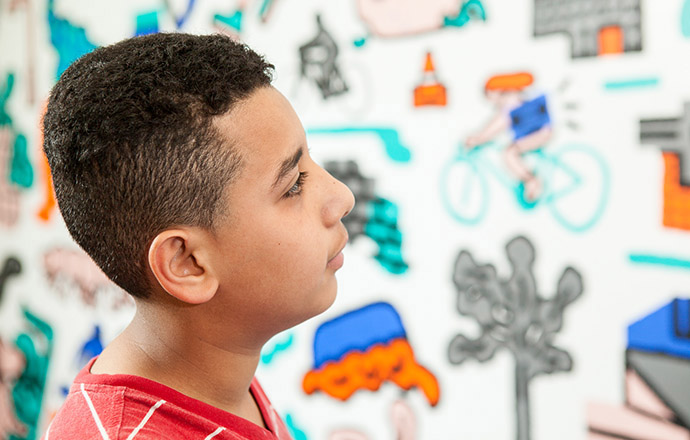<p>Ali looks at the PUMP mural on the wall at his school, admiring how it interpreted the poetry he and his classmates wrote. Photo by Craig Stokle.</p>