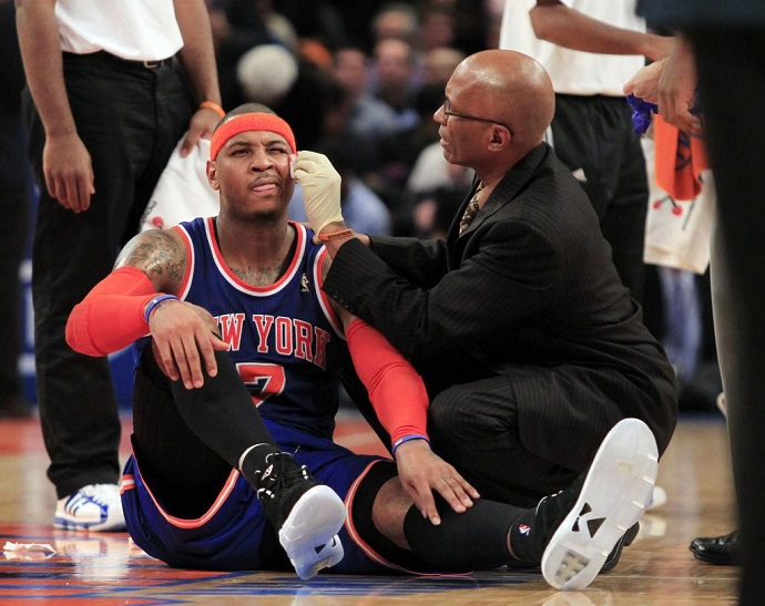 <p>NY Knicks Head Athletic Trainer Roger Hinds '77 tends to injured small forward Carmelo Anthony during a game.</p>